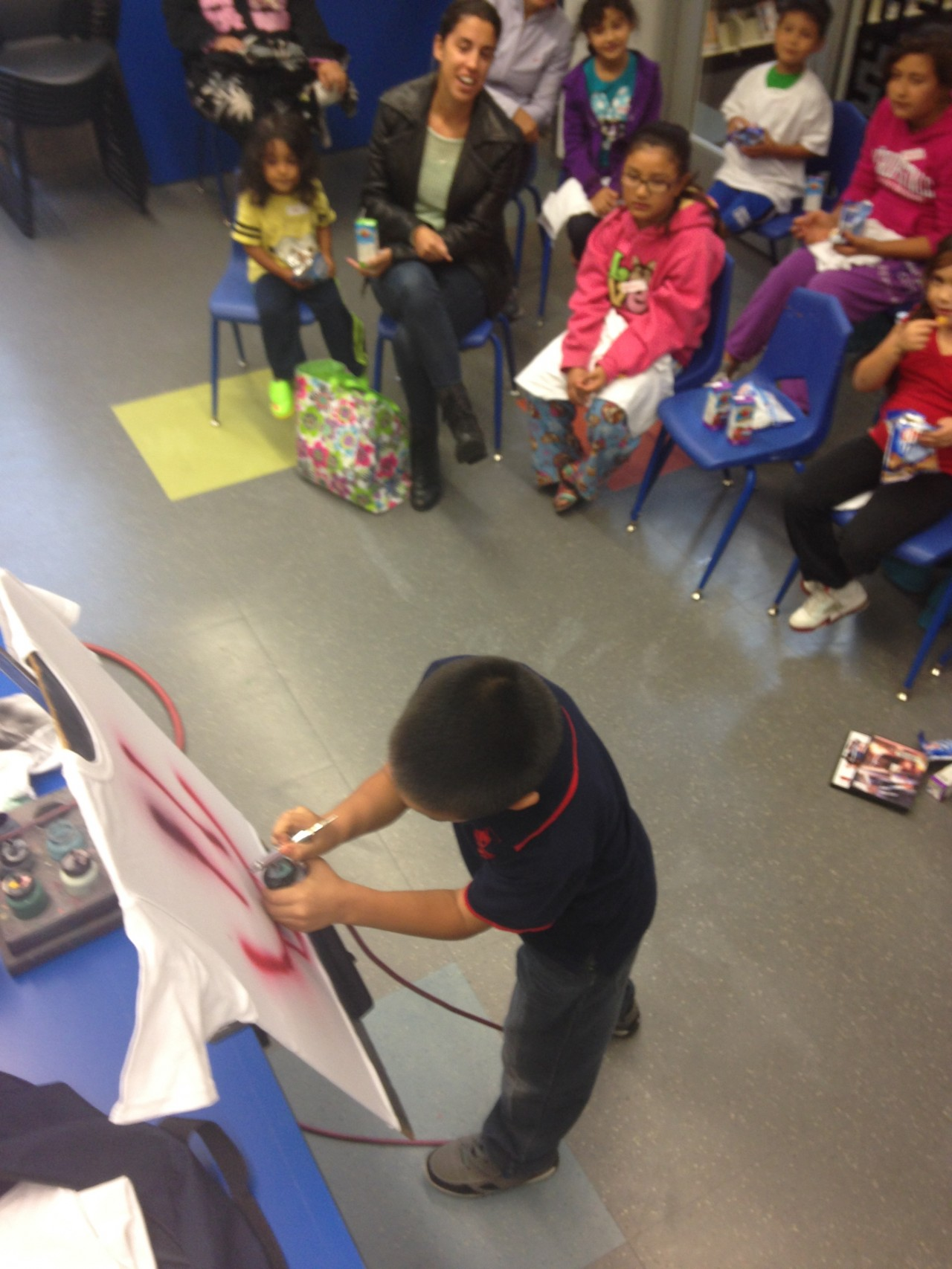 A little boy practicing his airbrushing techniques in the Summer Learning Program put on by the Denver Library